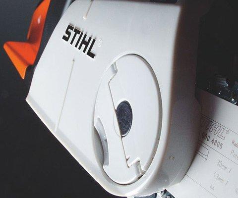 Das STIHL Kettenschnellspannsystem (B) macht das Spannen der Sägekette ganz einfach. Nach dem Lockern der Verschraubung des Kettenraddeckels lässt sich die Sägekette mit dem darüberliegenden Stellrad einfach und schnell spannen. Werkzeug wird dazu nicht benötigt. (Abb. ähnlich)