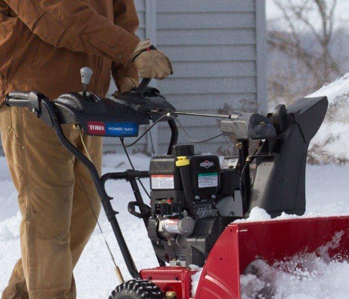 Einhändige Sicherung Bequeme Hebel ermöglichen den Betrieb mit einer Hand, sodass Sie mit der anderen Hand die Geschwindigkeit oder den Auswurfkanal anpassen können, ohne die Schneefräse anzuhalten.